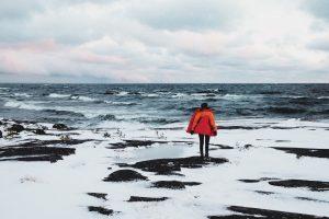 Kvinna i röd jacka ståendes och blickar ut mot ett vindpinat hav om vinden