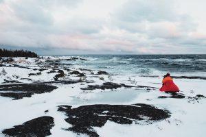 Kvinna i röd jacka som fotograferar ett vindpinat hav om vintern