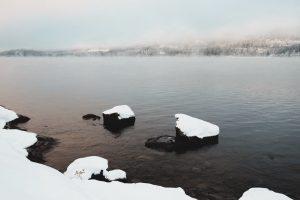 Snö på strandkant med stenar i vattnet och berg i bakgrunden