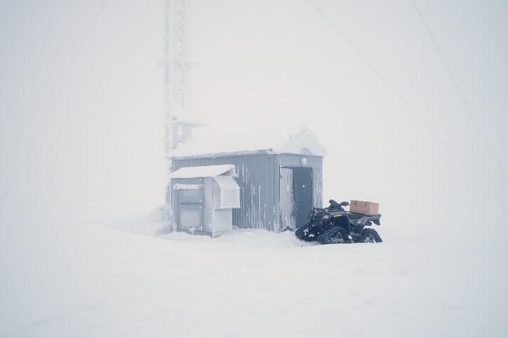 Fyrhjuling framför snötäckt skjul