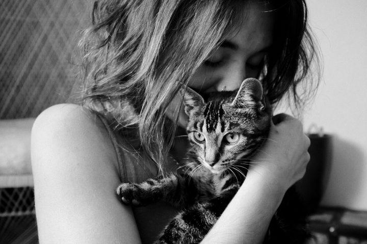 Person med katt i famn, svartvitt foto