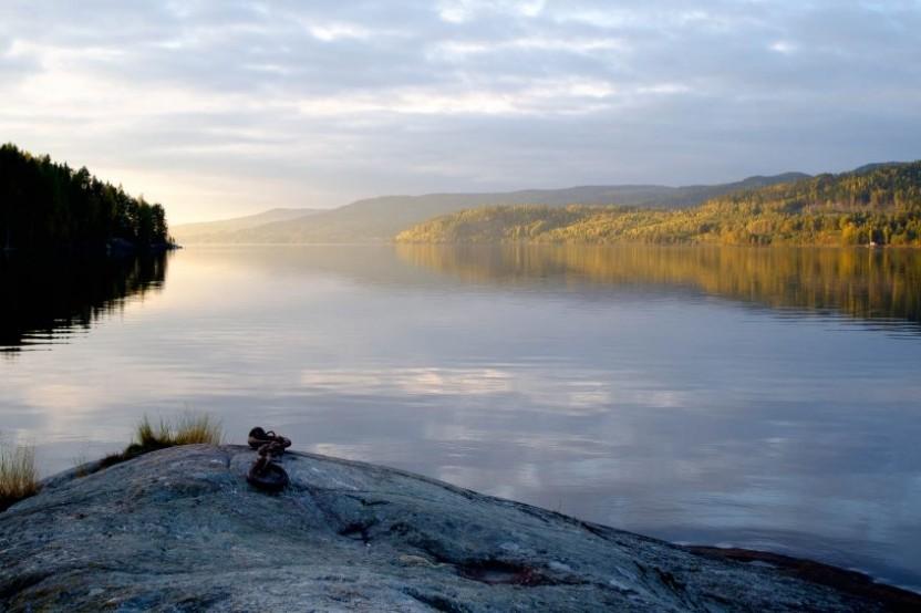 Utsökt över en sjö med sol som tittar fram och klippor i förgrunden