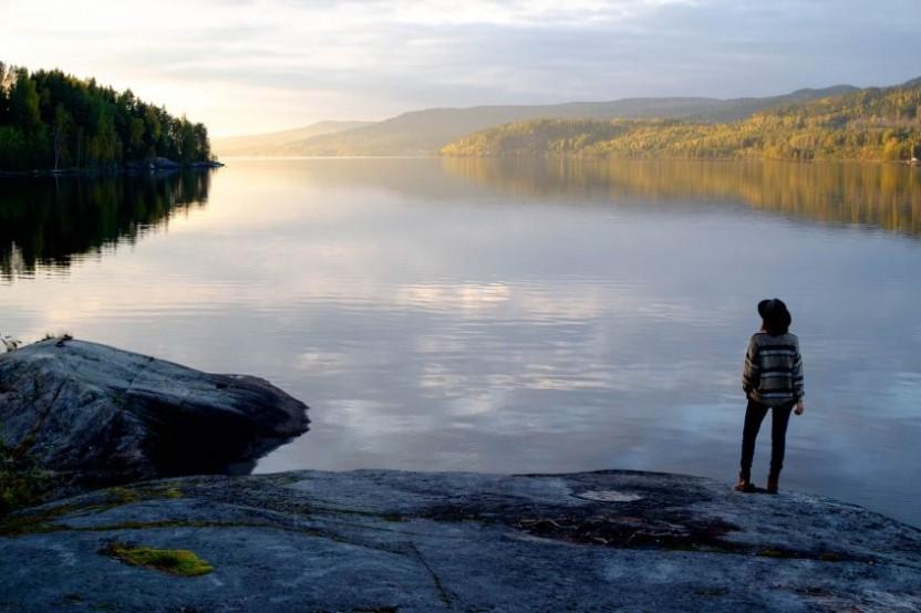 Utsökt över en sjö med sol som tittar fram och klippor och en kvinna i förgrunden