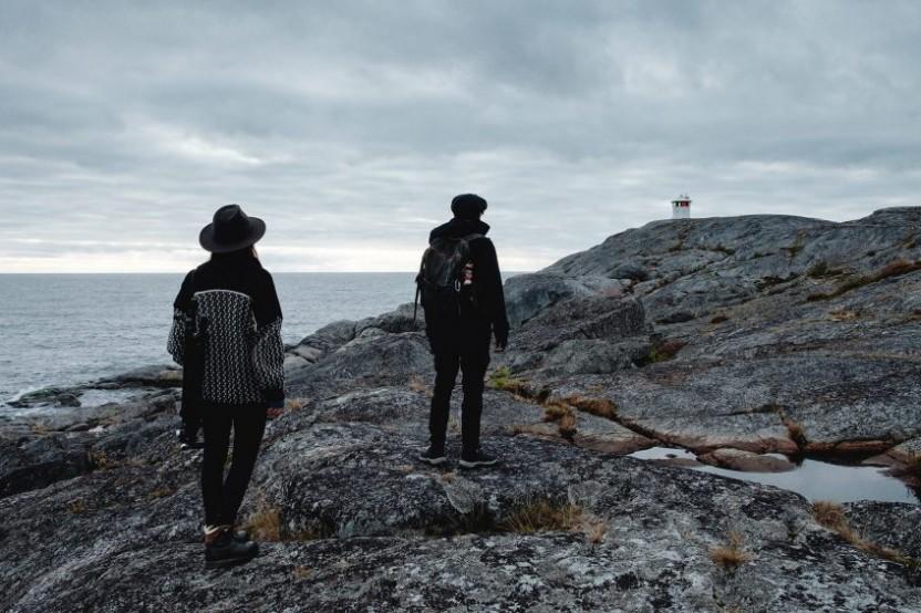 Kvinna och man på klippor med en fyr och hav i bakgrunden