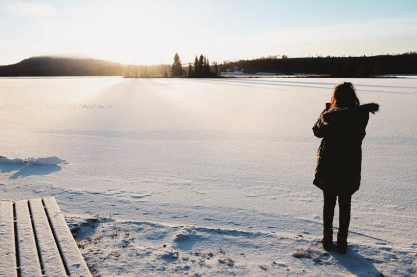Kvinna med kamera vid frusen sjö med solen över ett berg
