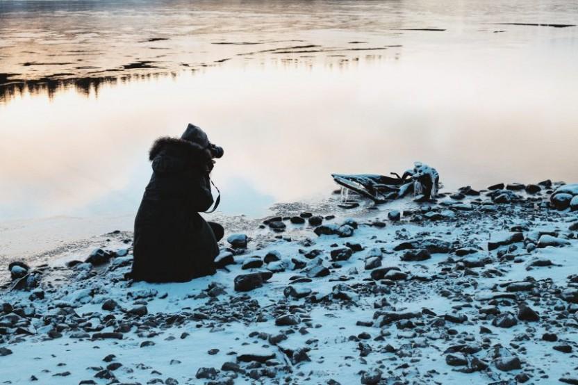 Kvinna med kamera på knä fotograferar frusen bit trä vid strandkant