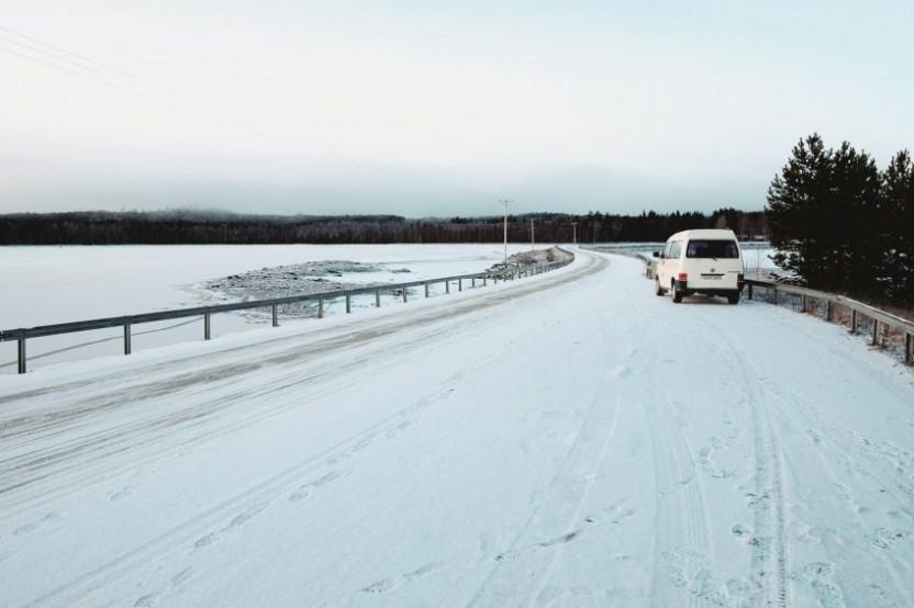 En wolkswagenbuss ståendes vid en vintrig vägkant med sjö till vänster