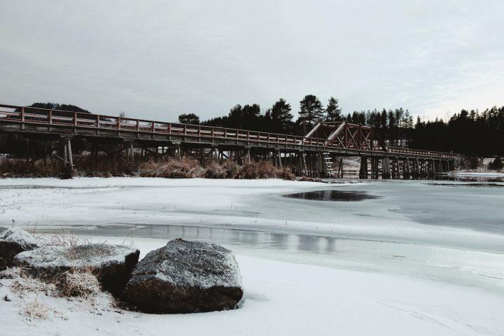 Bild föreställandes Vikbron, en träbro som går över älven Ljungan, med stenar i förgrunden