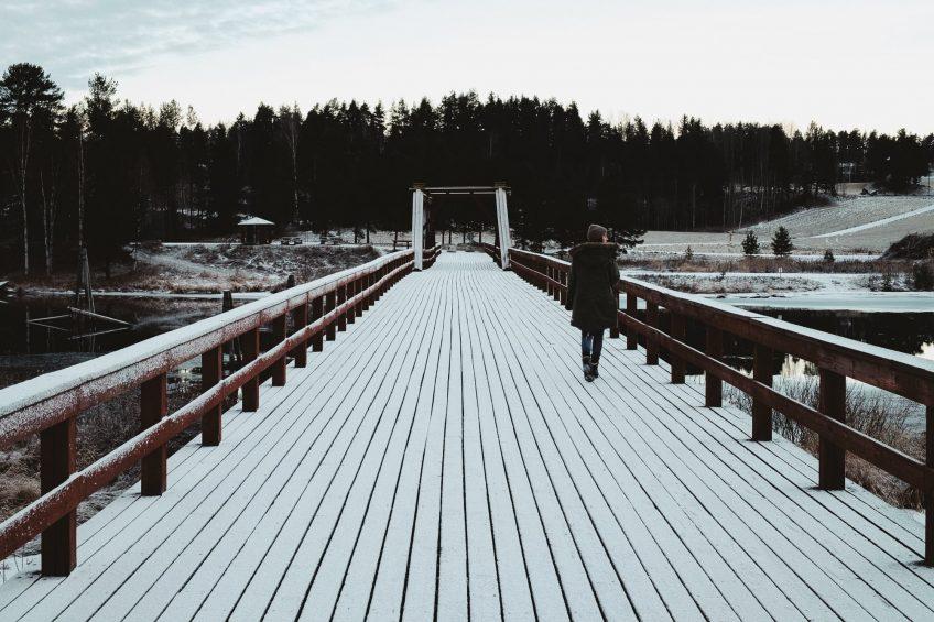 Kvinna gåendes över en lång träbro