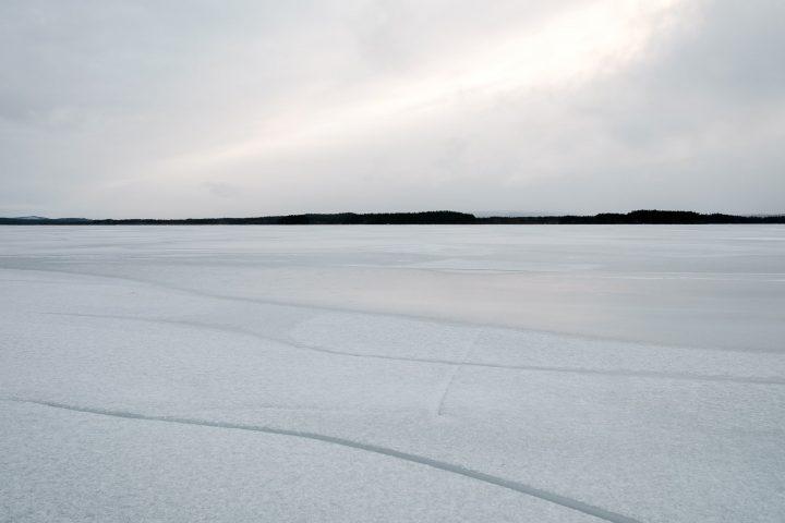 En frusen sjö med sprickor i isen och berg i den fjärran bakgrunden