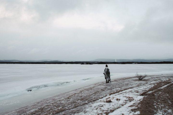 En kvinna i filt som står på en sandig strand vid en frusen sjö om vintern