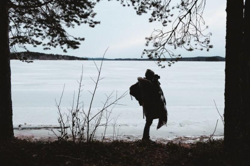 En kvinna som fotar med en frusen sjö i bakgrunden, det hela inramat av träd till vänster och höger